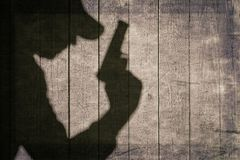 Black Armed Male Silhouette On The Wooden Fence. The Black Shadow Of A Man With A Handgun On The Wooden Wall. Black Armed Male Silhouette On The Wooden Fence Stock Photo