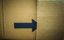 Black arrow on a cardboard shipping box for advertisement. Black arrow on a cardboard shipping box with some space for the text stock photos