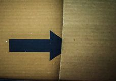 Black arrow on a cardboard shipping box for advertisement. Black arrow on a cardboard shipping box with some space for the text stock images