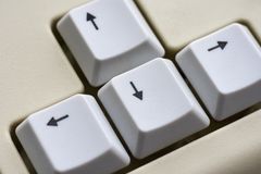 Black arrow on white buttons of a white keyboard close-up. Black arrow on white buttons of  white keyboard close-up Royalty Free Stock Image