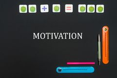 Black art table with stationery supplies with text motivation on blackboard. Concept school, black art table with stationery supplies with text motivation on Royalty Free Stock Images