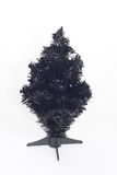 A black artificial Christmas undecorated. A black artificial Christmas tree on a stand against a white background Royalty Free Stock Photos