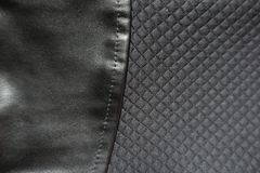 Black artificial leather sewn to polyester fabric. With relief checks Stock Photos