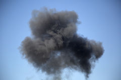 Black artificial smoke in the blue sky. Black artificial  smoke in the blue sky background Royalty Free Stock Images
