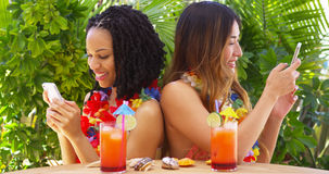 Black and Asian best friends on vacation using mobile phones Stock Images