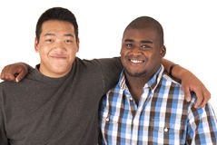 Black and Asian brothers with arms around each other smiling Royalty Free Stock Photo