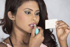 Black asian girl applying lipstick Royalty Free Stock Photo