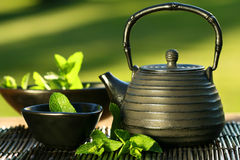 Black asian teapot with mint tea Stock Photography