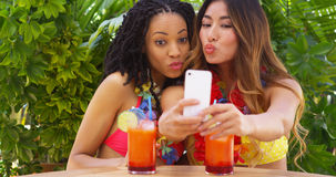 Black and Asian women taking selfie while on tropical vacation. Black and Asian women friends taking selfie while on tropical vacation royalty free stock image