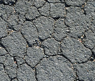 Black Asphalt Cracked. Background texture of cracked asphalt pavement. There are colorful pink orange and white rocks wedged in the cracks royalty free stock photo