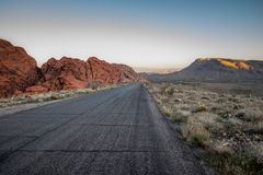 Black Asphalt Road Between Red Rocky Mountain and Green Grass Field Royalty Free Stock Photo