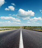Black asphalt road under deep blue cloudy sky Royalty Free Stock Image