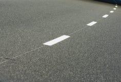 Black asphalt road and white dividing lines. Backgrounds stock image