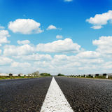 Black asphalt road with white line on center and blue sky Royalty Free Stock Photos
