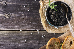 Black Astrakhan Russian salted sturgeon caviar in a can on dark background with wooden spoon and slices of bread. Snacks Royalty Free Stock Photos