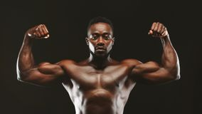 Black athlete flexing muscles, demonstrating strong biceps. Panorama royalty free stock photography
