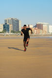 Black athlete running and training at the beach. Black fit man running and sprinting at city beach. Athlete training outdoor Stock Photo