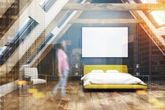 Black attic bedroom interior, yellow bed, girl. Gray attic bedroom interior with a wooden floor, windows in the roof, a yellow double bed with a white bedding Stock Photography