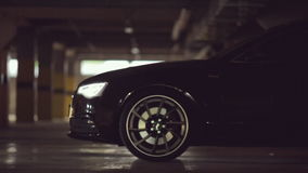 Black Audi leaves the parking lot with its lights. On HD 1080p stock video