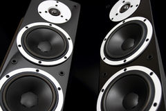Black audio speakers. Pair of black high gloss music speakers isolated on black background Stock Images