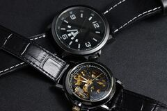 A black automatic self winding wristwatch with transparent sekeleton dial design and a black battery operated watch