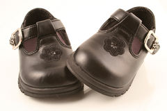 Black baby shoes 2. Black dressy new baby shoes - one on another royalty free stock photo