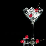 Black background with Cocktail glass, ice and cherries Royalty Free Stock Image
