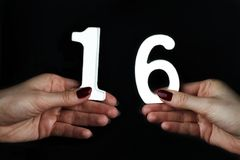 On the female palms figure sixteen. On a black background, female hand with number sixteen Stock Image