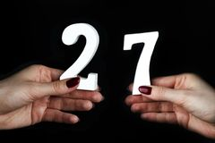 On the female palms figure twenty-seven. On a black background, female hand with number twenty-seven Stock Photography
