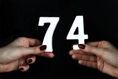 To female hands the figure of seventy-four. On a black background, female hand with numbers seventy-four Stock Image