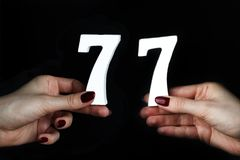 To female hands the figure of seventy-seven. On a black background, female hand with numbers seventy-seven Royalty Free Stock Photo