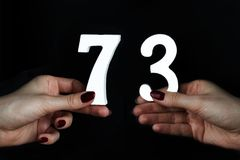 To female hands the figure of seventy-three. On a black background, female hand with numbers seventy-three Royalty Free Stock Photography