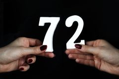 On the female palms figure seventy-two. On a black background, female hand with numbers seventy-two Royalty Free Stock Images