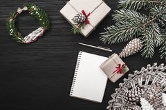 On a black background, a fir tree with cone, decorative objects. Christmas gifts and a note book, or for a holiday message. Royalty Free Stock Image