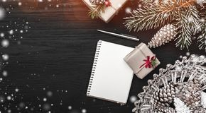 On a black background, a fir tree with cone and decorative objects. Gift and a note book or a Christmas message. Stock Photo