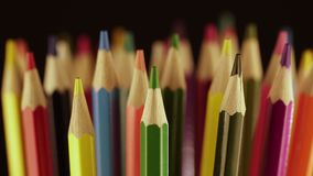 Bright colored pencils rotate in a glass around themselves. Close up. Macro. Macro shooting. Top of color pencils. stock video footage