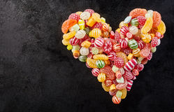Black background with heart shape made of candies Stock Photos