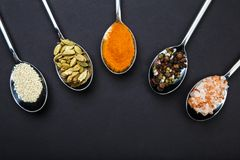On a black background with a horizontal arc spoons with spices are located. Royalty Free Stock Photo