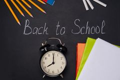 On a black background, with the inscription forward to school, on the table is an alarm clock, pencils and books for learning stock photos