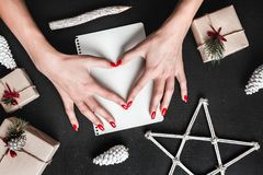 On the black background, a lady shows a heart on a white paper. Handmade gifts and Christmas atmosphere. Stock Photos