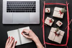 On black background, many gifts and computer. On a book, a lady`s hands. Royalty Free Stock Images