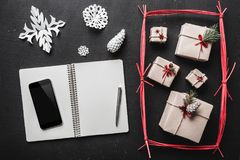 On the black background, many gifts and handmade items, a booklet where you can copy a greeting message from your phone. Top view stock photography