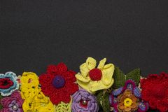 Black background and multicolored knitted flowers from below stock photography