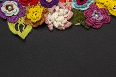 Black background and multicolored knitted flowers on top stock image