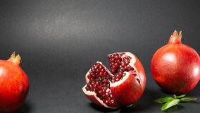 Black background, in the photo there are three pomegranates fruit in the middle of the rosewood and pomegranate grains are visible stock photos