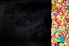 Black background with pile of candies to one side Stock Images