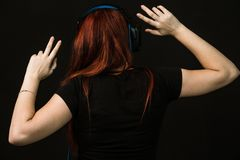Redheaded woman with blue headphones is dancing stock photo