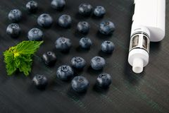 On a black background ripe berries with mint for electronic cigarette taste stock photography