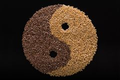 Flax seeds are laid out in the form of Yin-Yang. On a black background seeds black and white flax laid out in the form of the Yin Yang symbol Royalty Free Stock Images