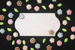 On a black background small flowers made of paper are randomly scattered. In the center is an empty plate with copy. Space. Photo with space for text royalty free stock images
